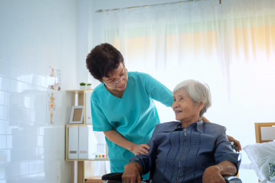 Delighted positive caregiver helping her patient at home